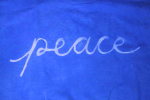 image of blue-dyed shirt with the word peace written in white